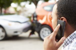 Man at a crash scene on the phone with Long Island car accident attorneys.