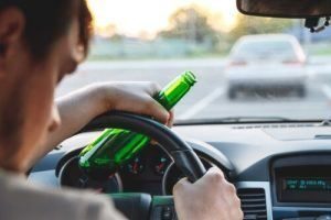 Drunk driver holding a bottle of alcohol