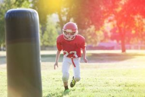 young boy practicing football