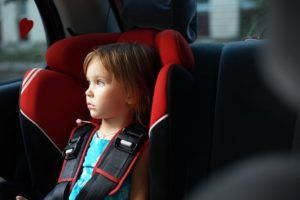 child on a car seat looking outside
