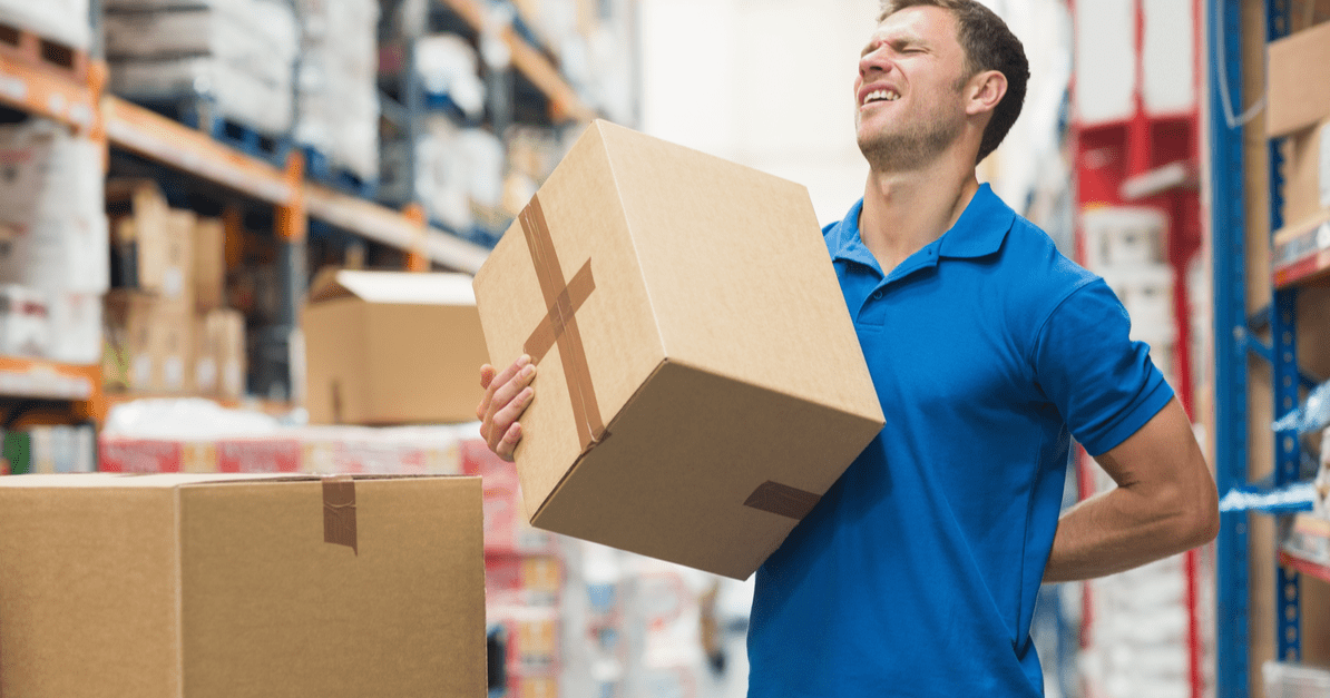Man suffering from overexertion injury for lifting heavy boxes
