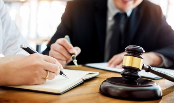 truck accident attorney holding a pen with papers and gavel and hammer in front of him