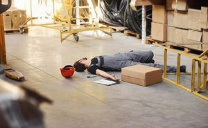 a warehouse worker laying on the floor unconciously after he fell on a steel stair with his red hard hat above his head and a box , ballpen and papers scattered around him - workers common injuries