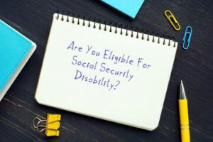 writing pad with the word -are you eliginle for social security disability- with paper clips, and pen around