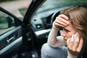 woman calling on her phone after a car accident