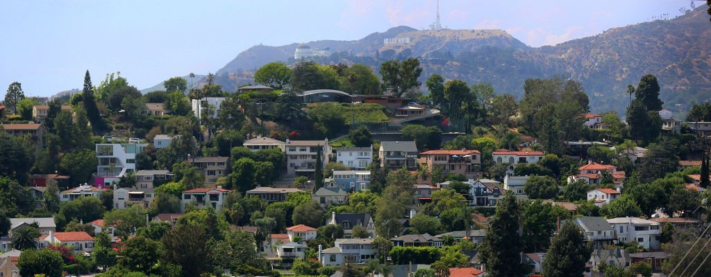 A hillside full of homes of a variety of architectural styles in front of the Griffith Observatory and Hollywood Sign in Silver Lake, Los Angeles, California