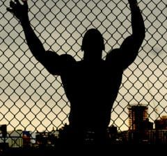 Outline of muscular man leaning against a chain link fence looking over a city