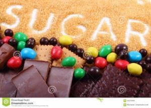 """Pile of chocolate, cookies, candy and brown cane sugar with word """"sugar"""" spelled out"""