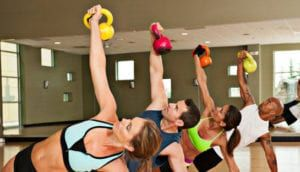 Workout class of men and women with kettle bells in gym