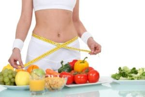 Woman in white workout clothes measuring hips with yellow tape measure by clear table with three plates of fruits, vegetables, orange juice, and cereal