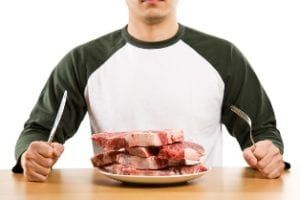 Man wearing green and white baseball shirt holding fork and knife sitting front of plate of four raw steaks