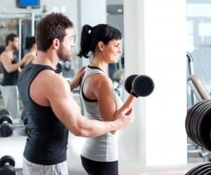 Young dark-haired young woman lifting dumbbell with help of young brown hair male personal trainer