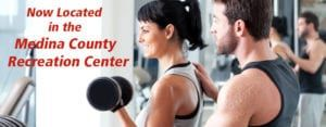 Black-haired young woman lifting weights with young male personal trainer helping in gym with red lettering about Medina County Recreation Center