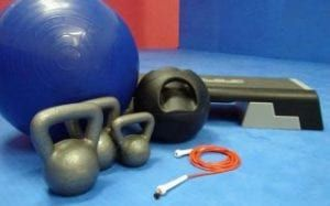 Three gray kettle balls, orange jump rope, blue exercise ball, black medicine ball, black step in blue and red gym