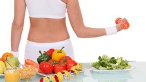 Woman in white workout clothes in lifting dumbbell behind table with veggies, fruit, cereal, orange juice, and yellow tape measure