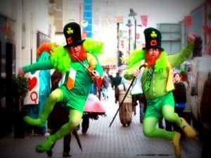 Two men dressed as red-bearded leprechauns in green doing heel click jump on city street