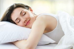 Burnette, smiling, young woman wearing white tank top hugging white pillow under white blanket sleeping in bed