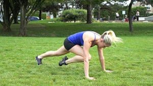 Young blonde woman in black and blue doing mountain climbers outside in park