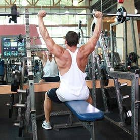 Muscular man lifting barbell on blue bench in gym