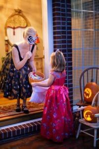 woman in black dress holding cany bowl out to girl trick or treating in pink dress