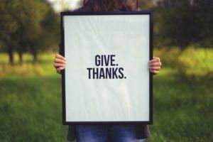 Person holding black framed give thanks sign outside in early fall