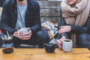 man in black jacket holding coffee cup and young woman in tan scarf sitting outside drinking coffee