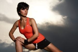 Young dark haired woman with short hair wearing orange tank top and black shots doing lunges on cloudy day