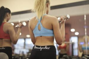 Two women in black leggings, red and blue workout bras lifting weights in front of mirror at gym