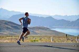 Man wearing blue and black running on road with mountains and lake in background
