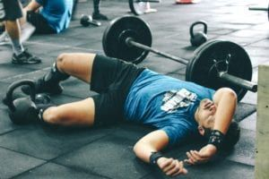 Tired man wearing blue and black laying on tile floor by barbells and kettle bell after working out