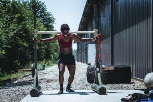 Young woman wearing red and black while lifting weights outside