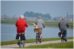 Two elderly people in gray biking and one elderly person in red biking along lake with town in background