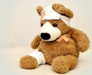 Brown furry teddy bear wrapped in bandages
