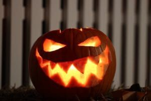 Scary face jack-o-lantern lighted by candle outside in front of white picket fence