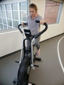 Young woman working out on exercise bike