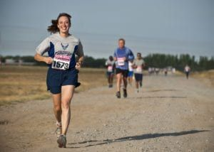 Woman in blue running ahead of group of other runners outside on a dirt road