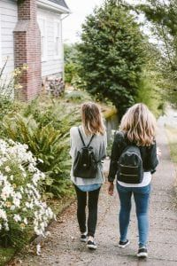 Two young women in jeans, sweater, and backpacks walking along garden near house