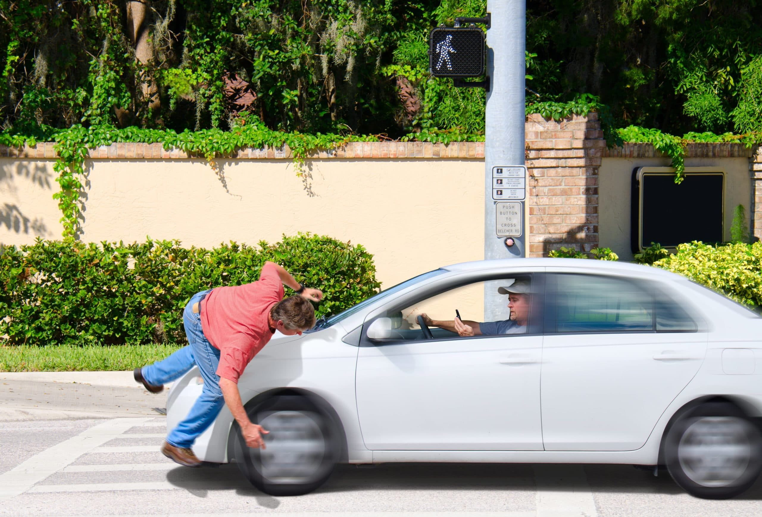 Distracted driver hit a man walking in pedestrian lane.
