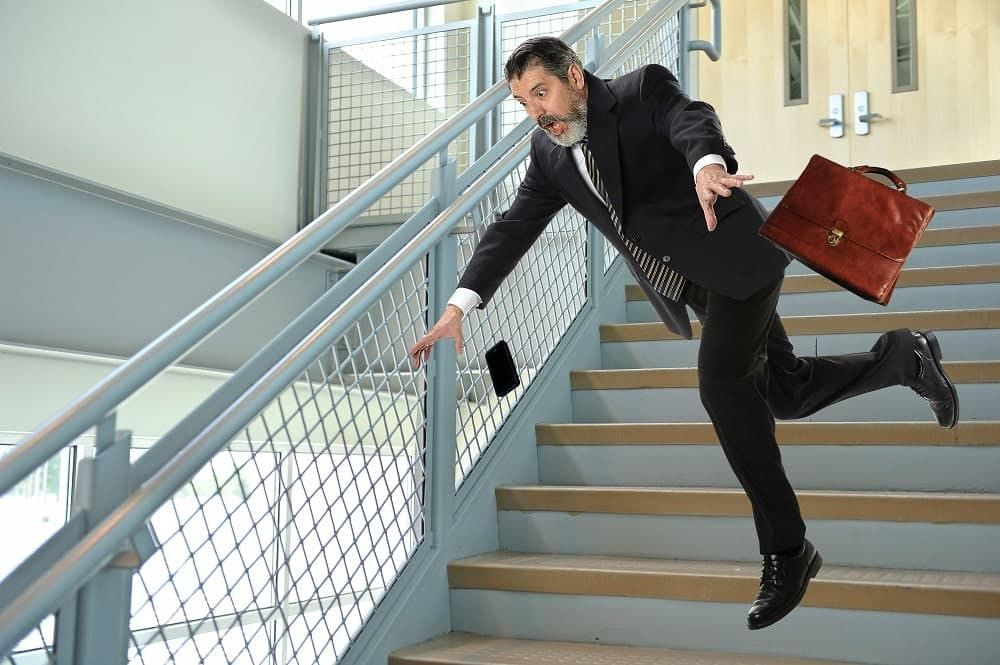 Businessman fall off the stairs going to parking lot.