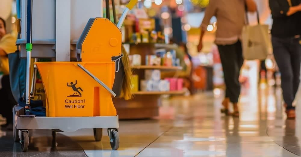 Yellow mop bucket floor cleaning equipment and mops in shopping mall.