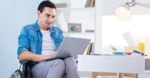 Man in wheelchair applying online for social security disability claim.