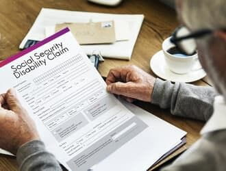SSD lawyer in Denver reads paperwork for a social security disability claim.