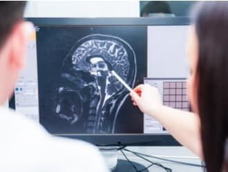 A doctor and a Denver brain injury lawyer look at a scan of a TBI.