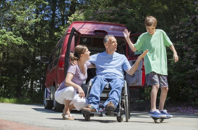 Man with spinal cord injury in a wheelchair with family