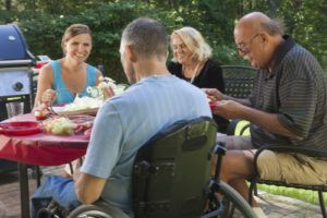 Man with spinal cord injury in wheelchair at family outdoor