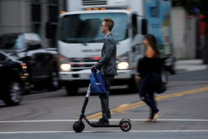 A man in a suit rides an electric BIRD rental scooter along a city street in San Diego, California