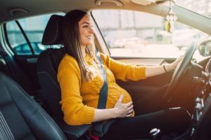 Pregnant woman driving in the highway.