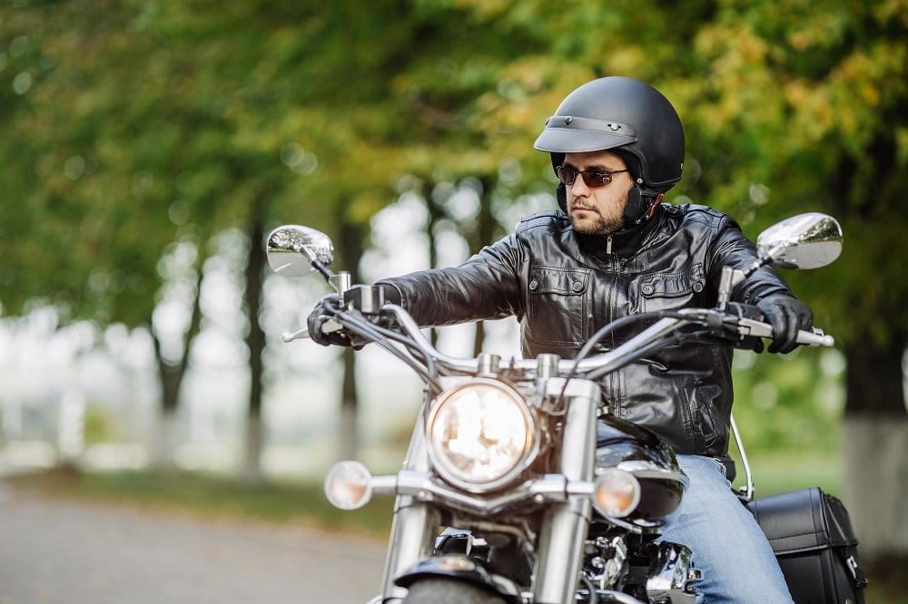 Motorcycle rider wearing helmet and safety gear.