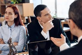 Young divorcing couple looks in different directions, listening to lawyer who sitting at table.