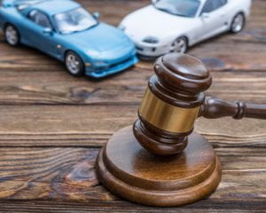 Car accident lawyer concept with gavel at the center.